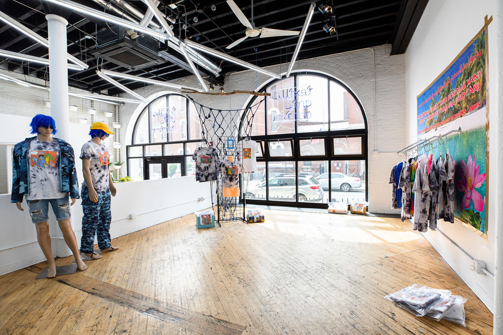 A site-specific installation resembling the interior space of a clothing store. Across a series of beach and tropical-themed retail displays are t-shirts that are available for purchase.