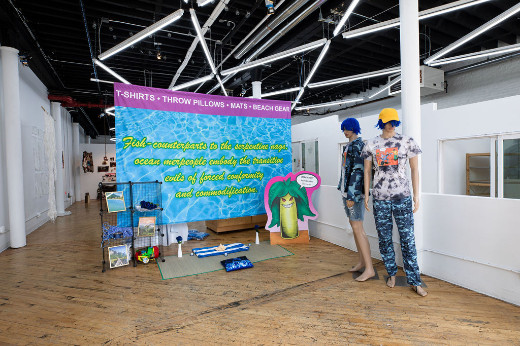 A site-specific installation resembling the interior space of a clothing store. Across a series of beach and tropical-themed retail displays are t-shirts that are available for purchase. In the center of the installation is a large blue sign hanging behind the display, along with two mannequins wearing the various clothes designed by the artist.