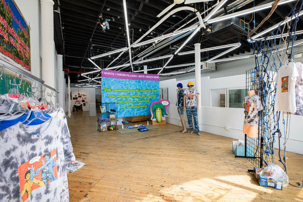 A corner shot of a site-specific installation resembling the interior space of a clothing store. Across a series of beach and tropical-themed retail displays are t-shirts that are available for purchase.