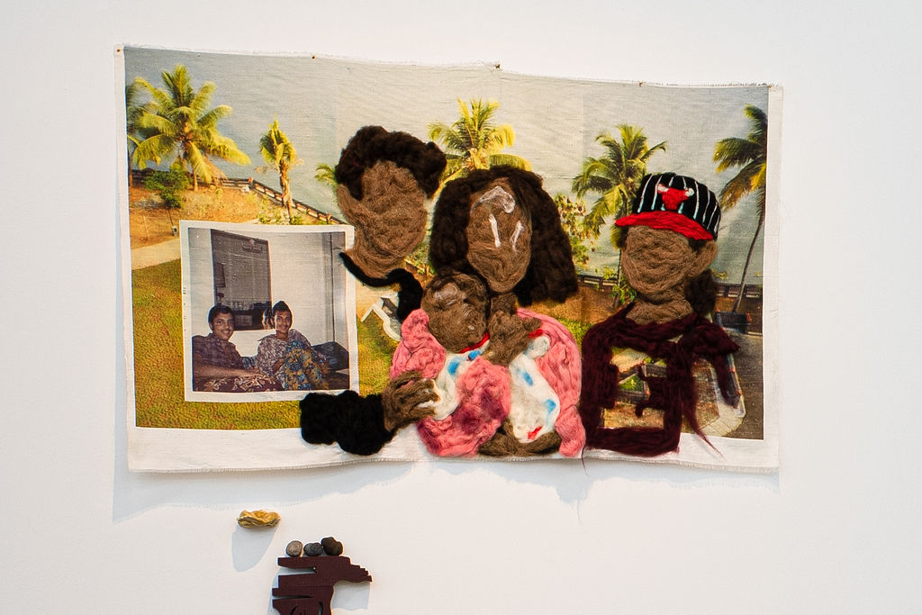 Felted family portrait on a printed fabric with a tropical beach scene. There is a square photograph of two people in the bottom left corner of the printed fabric.