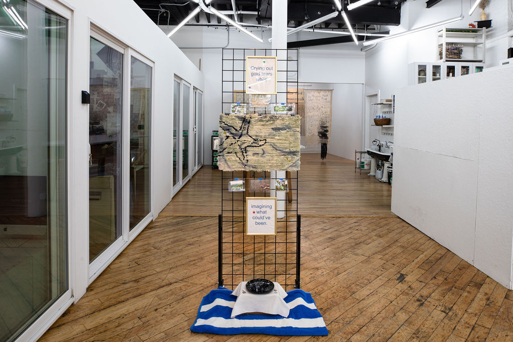 "A wire grid display standing in the middle of the floor with the following images and objects attached to it: small laminated photos of rainforests and starfish; two gold-framed texts that read ""crying out gold tears while,"" and ""imagining what could've been""; and a hand-tufted mat. The mat depicts a starfish, and it has had a face painted onto it with gold embroidered tears falling from the eyes. On the floor in front of the display is a towel and a small table with a plate of blueberries."
