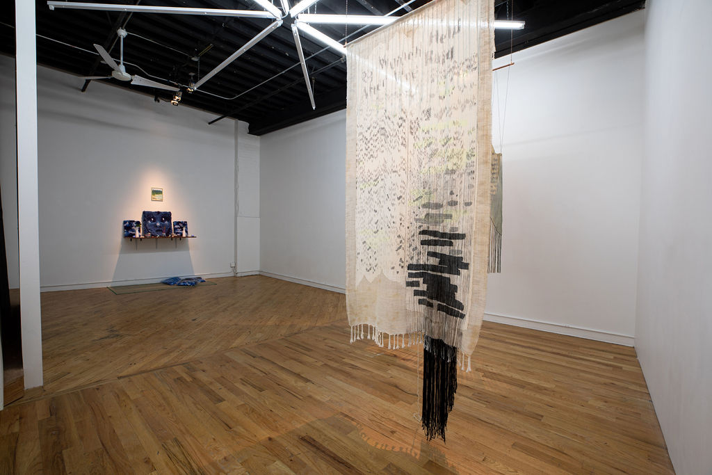 View of Subtle Speaks exhibition at the Textile Arts Center, showing the work of Cong-Tam Nguyen on the back left wall and Rowan Renee on the right.