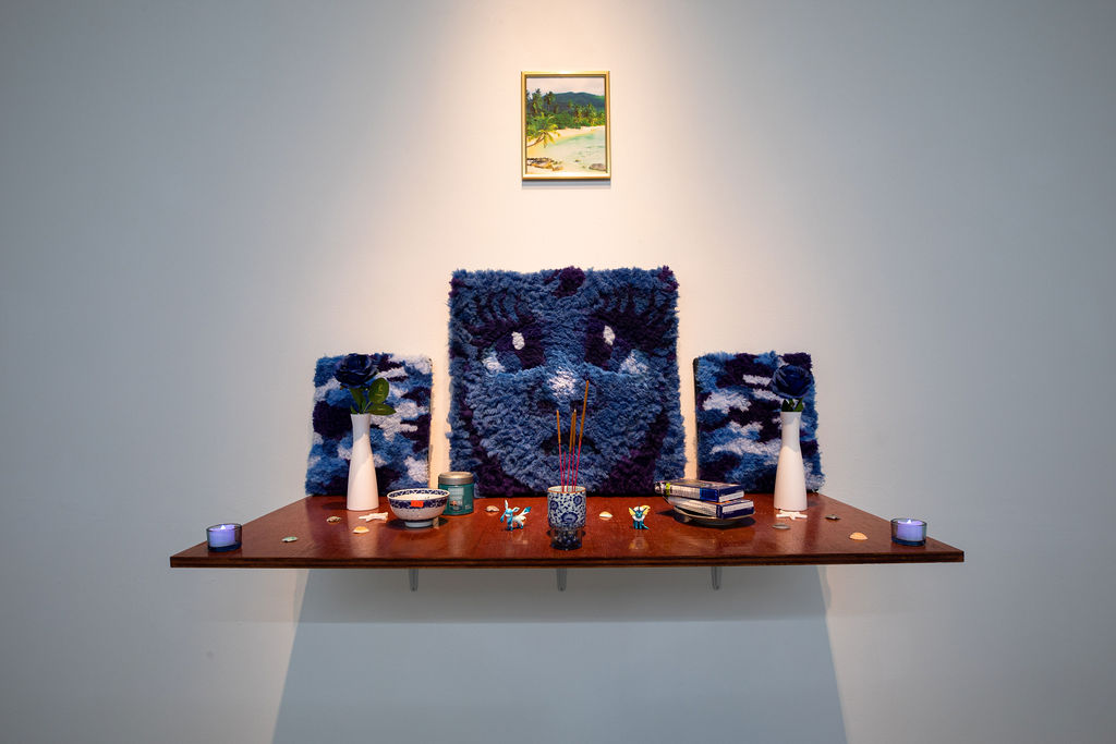 A panel of stained wood jutting out from the wall, with objects placed on it and arranged like an altar. In the back--leaning against the wall--are three blue hand-tufted pieces stretched like paintings. A gold-framed photo of a tropical beach hangs on the wall above. The objects in front of tufted pieces include flowers in vases, seashells, starfish, dinnerware with blueberries and blueberry-flavored foods, incense, Pokemon figurines, and blue LED candles. Beneath the altar is a straw beach mat with pillows that have been wrapped in plastic protectors.