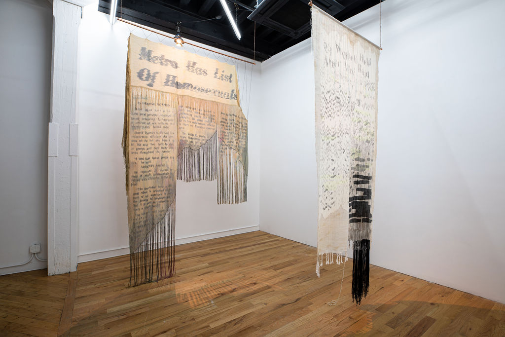 Large tapestry reproduction of newspaper clipping with text. The words are blurred almost to illegibility on light colored fiber with patches of black inlay redaction.