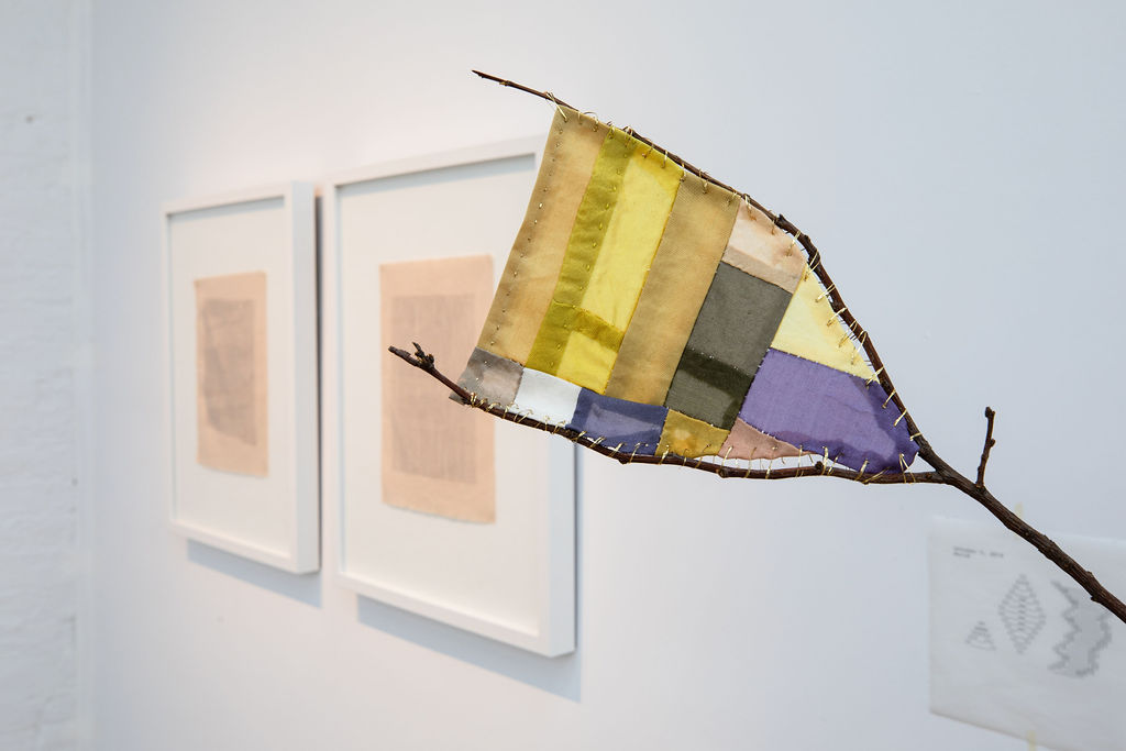 A thin tree branch with a small patch of quilted fabric sewn into one of its gaps. The quilted fabric has yellow, purple, dark green, and peach colors, held to the tree branch by gold thread.