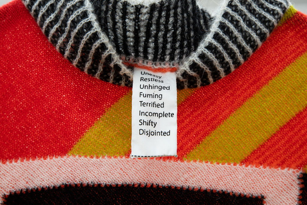 Close up of a knitted sweater with green and white stripes on the collar and diagonal orange and yellow stripes below the collar. A long white tag with text hangs from the collar of the sweater.