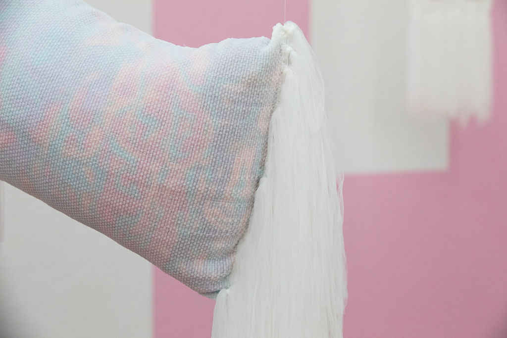 A rectangular throw-sized transparent pillow stuffed with pink, purple, green and orange yarn snips suspended at an angle with soft tulle yarn fringe falling from both ends.