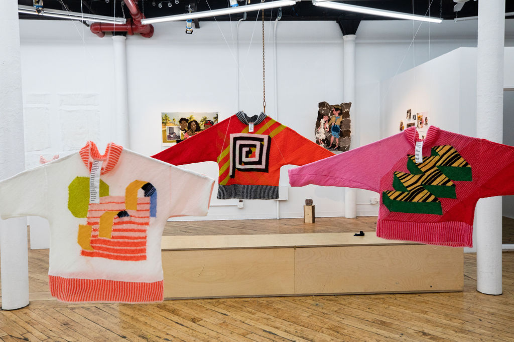 Three knitted sweaters hanging from the ceiling with colorful geometric designs of orange, red, pink, green, white, and yellow.