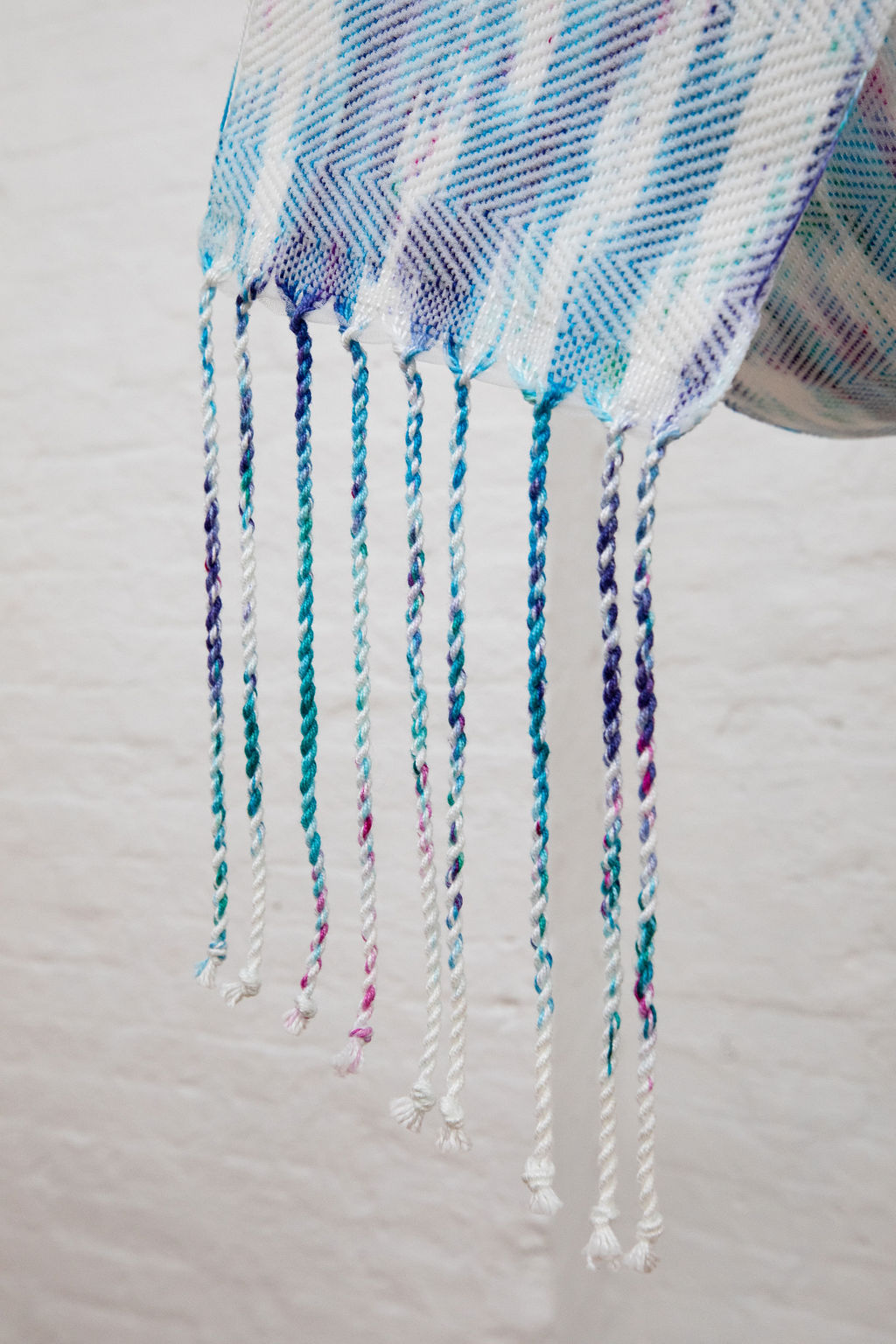 A long, thin hanging draped and suspended in the air is splattered with red, blue, purple and green dye and woven in a semi-transparent zig-zag design.