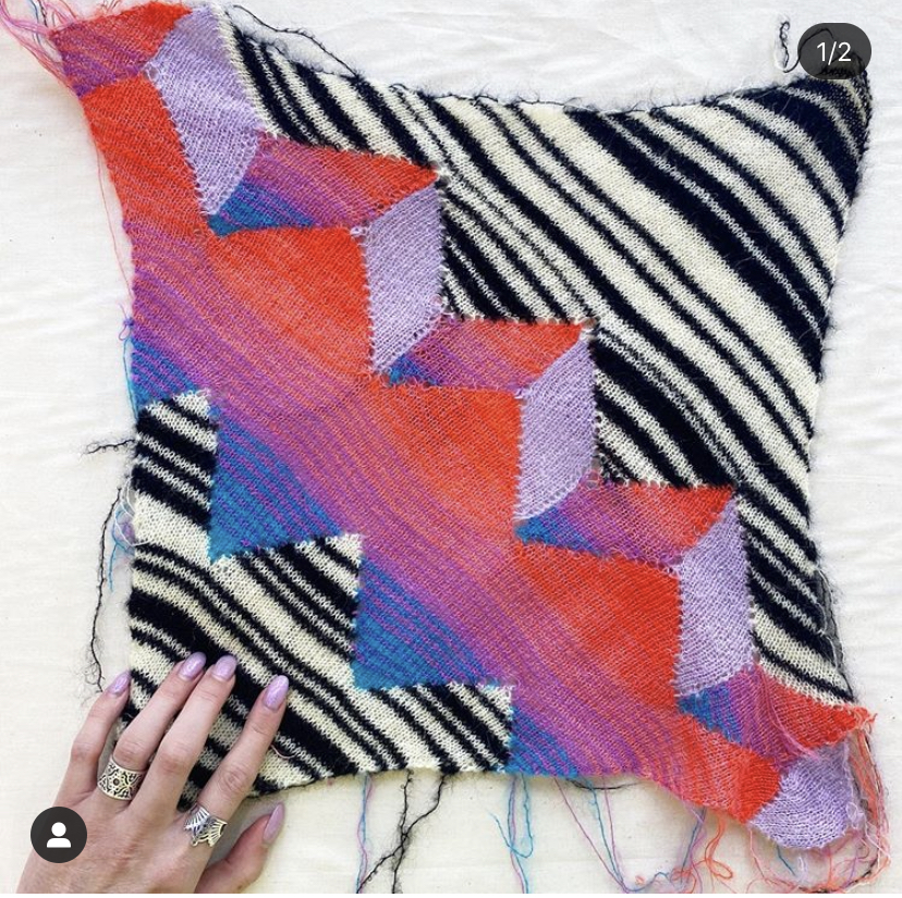 A hand touching the corner of a piece of Marta's knitwear, patterned with colorful prisms over black and white stripes.