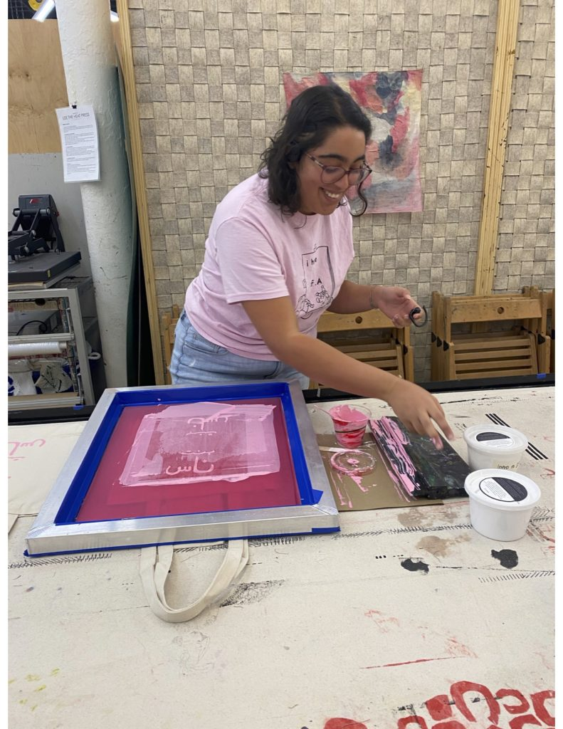 Zuhoor at work screen printing in the TAC studio