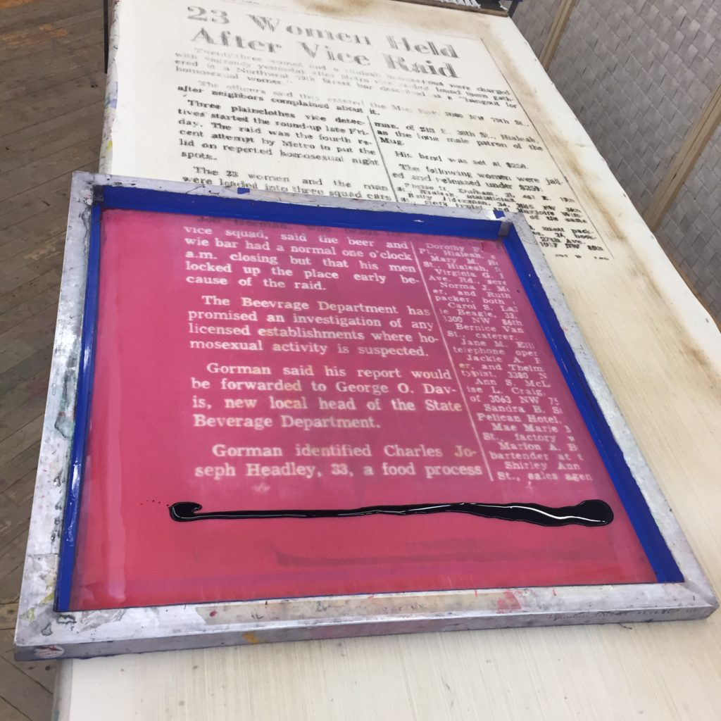 Rowan's work; plaque of a newspaper clipping enframed over their tapestry with another newspaper story regarding queer history and surveillance