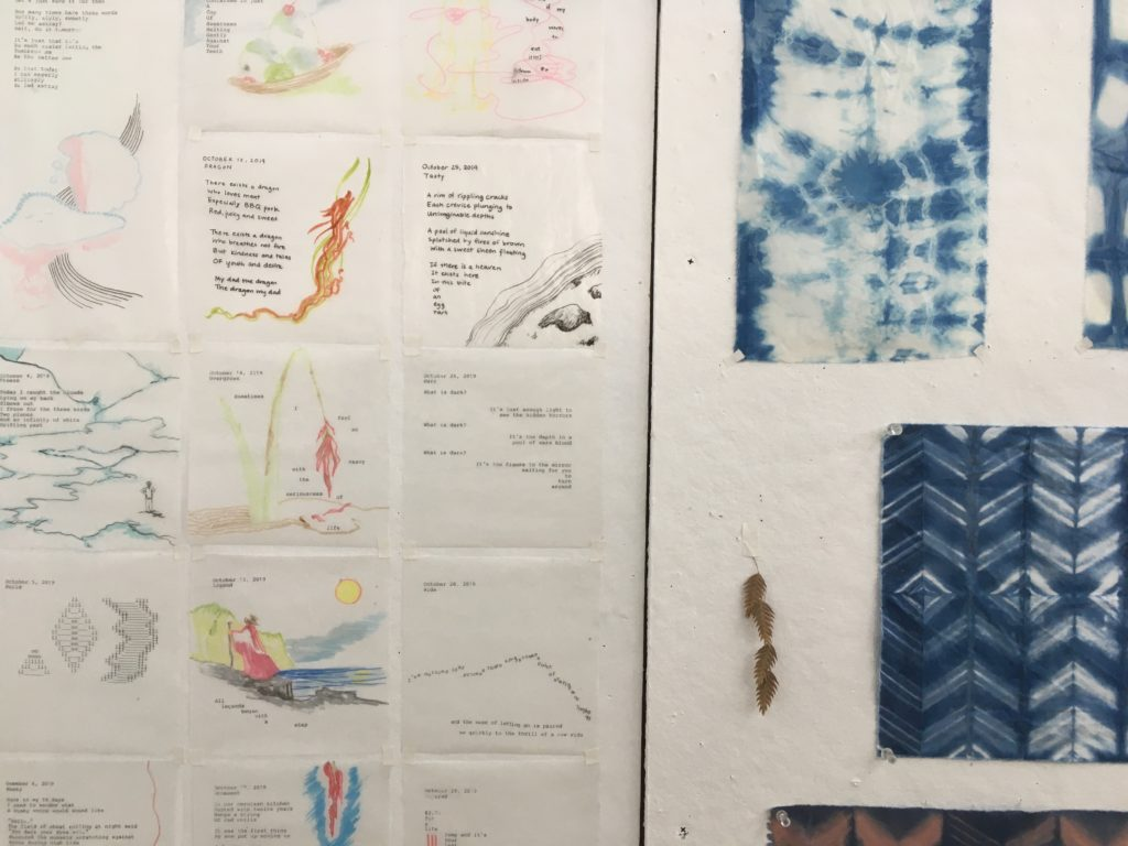 Close-up image of Yidan's work space at TAC; swatches of fabric, small poems and sketches tacked to the wall