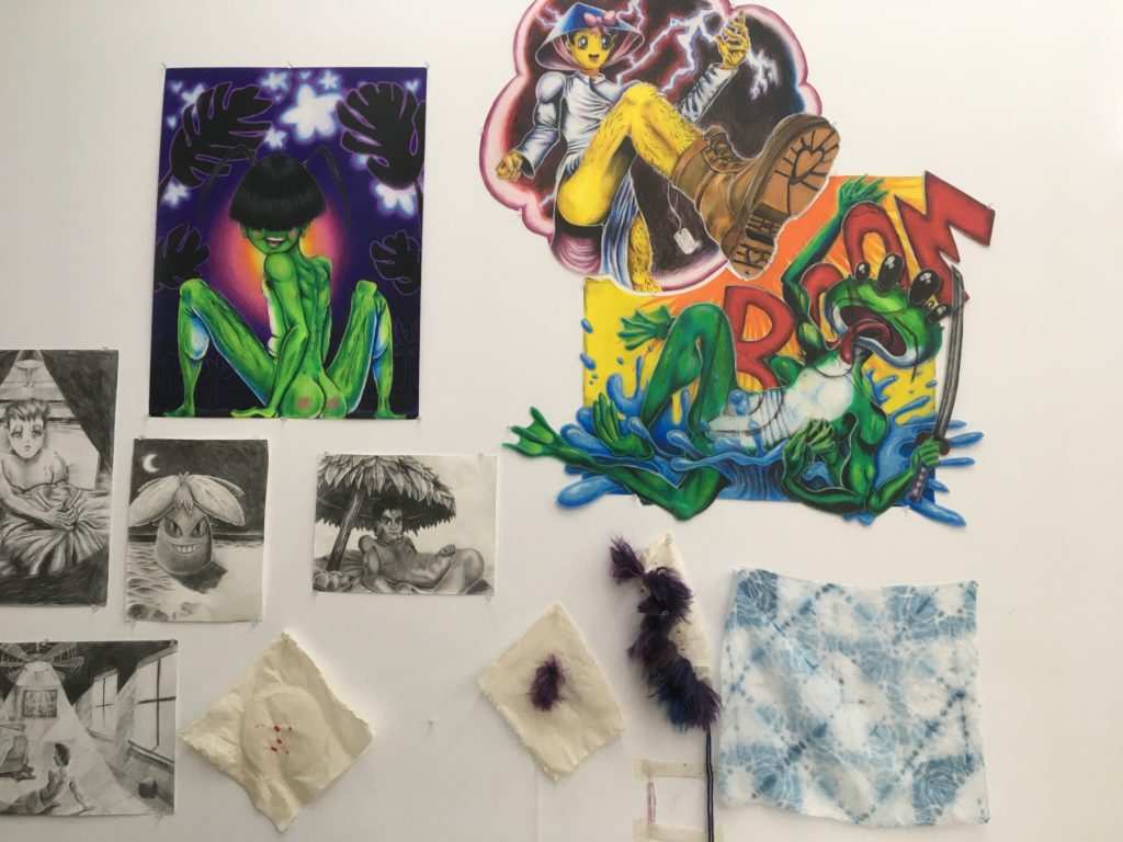Tam's work space at TAC; close-up of wall with sketches, other images, and swatches of fabric