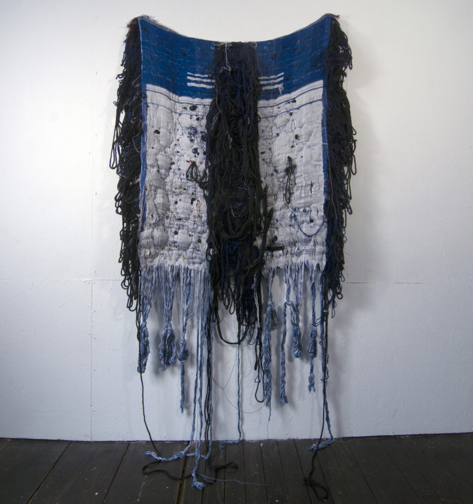 A large blue and white tarp-like textile hangs from the wall with blackish and whitish fraying around its perimeter and down its center.