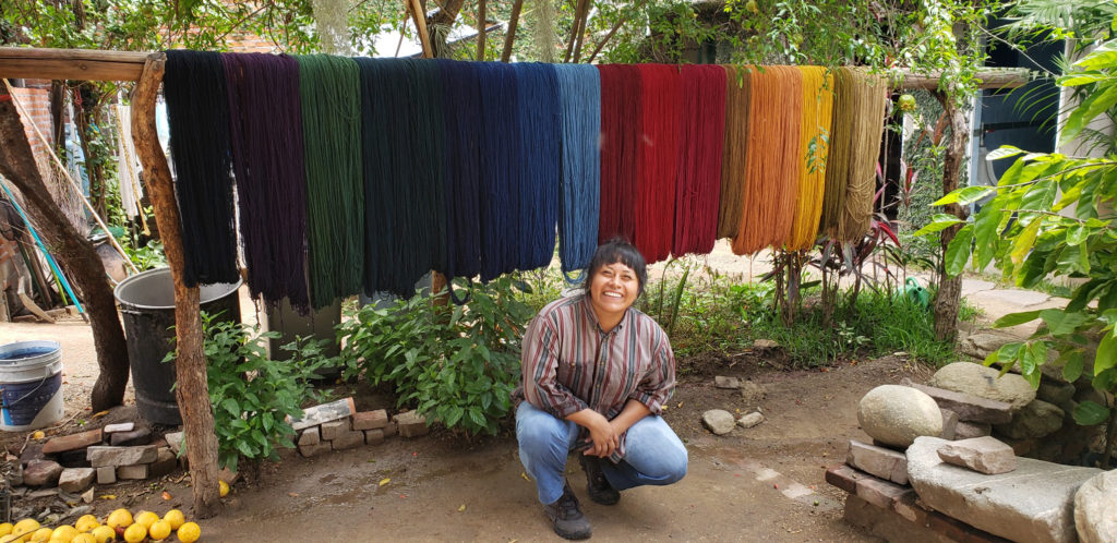 Jessica squats in front of a small village setting in front of variously dyed batches of yarn.