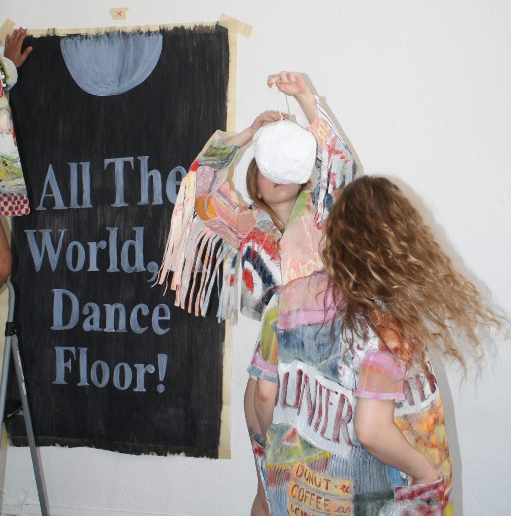 "Two women in brightly printed, pastel-like, clothing face each other, both of their faces obscured (one obscured by a white object she is holding, and the other with her back to the viewer). Behind them, a hand it putting up a black poster stating, ""All The World, Dance Floor!"""