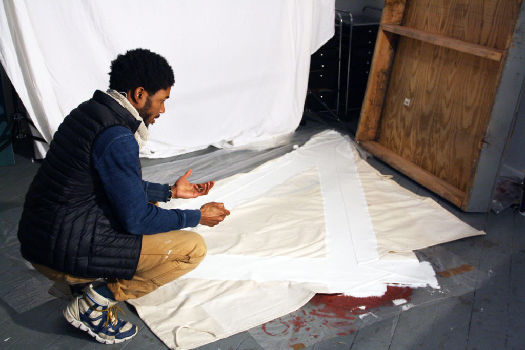 Ryan crouches in front of a spread of white cloth on the floor