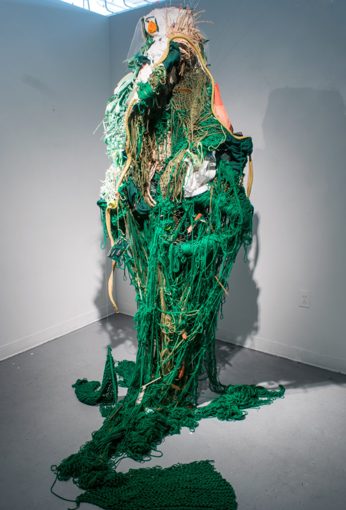 A mass of mostly green yarn pours out of an ovular shape, bounded by rope that hangs from the ceiling, and spills onto the floor